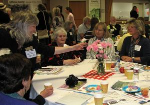 Deborah Andrews reaches to add a carnation; carnation color sorted participants into discussion groups.