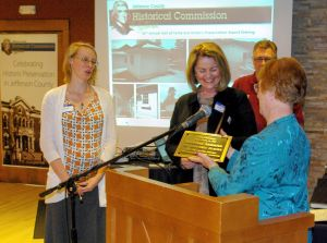 Suzi Morris, of Conifer Historical Society and Museum, accepts National Register plaque from Rita Peterson.