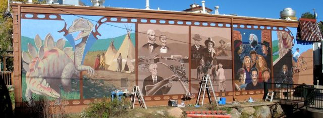 The Morrison mural, completed by Emanuel Martinez in 2007, has six panels depicting dinosaur days, Native American culture, early European settlement and dinosaur discovery, early 20th century film-making and tourism, Red Rocks Amphitheatre performers, and outdoor recreation.