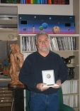 Surrounded by artwork in his studio, Emanuel holds one of his many awards.