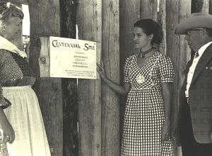 Hazel Humphrey, left, presents Centennial Site plaque to [unidentified] and Elmer Wyland of Fort Westernaire, 1975, on behalf of the Historical Commission.