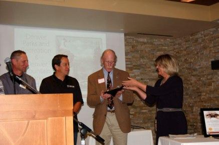 JCHC Chair Cynthia Shaw presents the 2017 Meyer Award to Bart Berger, DMP Foundation. Brad Eckert and Scott Gilmore, representing co-awardee Denver Parks & Rec, left.